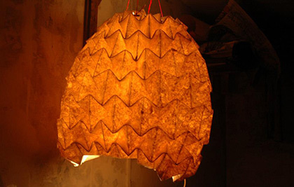 A spherical lamp made of a repeated folding pattern.