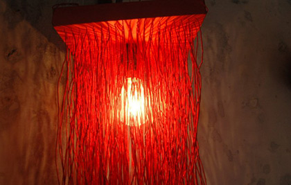 A pendant lamp made up of hanging strings.